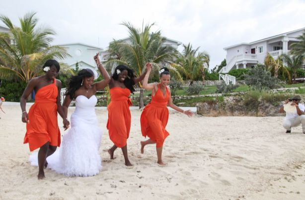 Bride and bridesmaid running on the beach